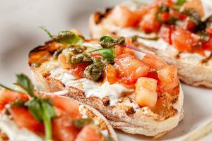 Italian cuisine, antipasti and tapas. Bruschetta of baguette and cottage cheese, tomato, capers, pesto. Serving dishes in a restaurant in white plate. background image, copy space
